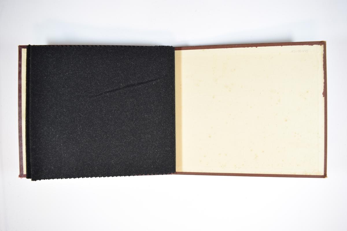 Prøvebok med 2 stoffprøver. Middels tykke og mørke stoff. Begge stoffene er tovet/valket, og ligner vadmel. Stoffene ligger brettet dobbelt slik at vranga skjules. Stoffene er merket med en rund papirlapp, festet til stoffet med metallstifter, hvor nummer er påført for hånd.   Stoff nr.: 660/12, 661/14. Undernummerene har imidlertid blitt rettet til: 660/10 og 661/11.