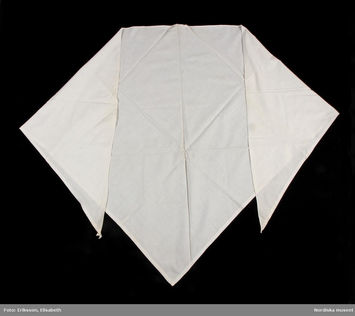 """Huvudliggaren: """"Axelschal, stor, kvadr, hvit, 'sorgpålägg'.  Utdrag ur bilaga """" 'Sorgplagg', till sorgdräkten, att hava öfver axlarna med mössa och 'slätstycke' och svart klädning.""""  Katalogkort:  Stort halskläde, vitt, i tuskaftad bomull. Tresidigt, två kortsidor och en långsida. Klippt på tvären av en kvadratisk tygbit. Korstidorna har 1,5 cm bred fåll, långsidan 3 mm bred fåll. Halsklädet är handsytt. /Inga-Lill Eliasson 2008-02-11"""