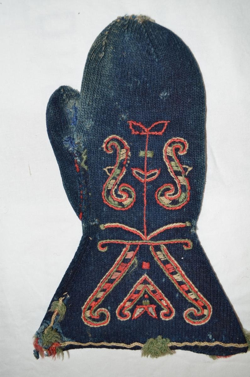 Valdresvott av strikka blått handtvinna ullgarn. Brodert med ullgarn på framsida i rødt, gult og grønt. Utskrådd ermekrage. Frynser i sidene og midt foran.