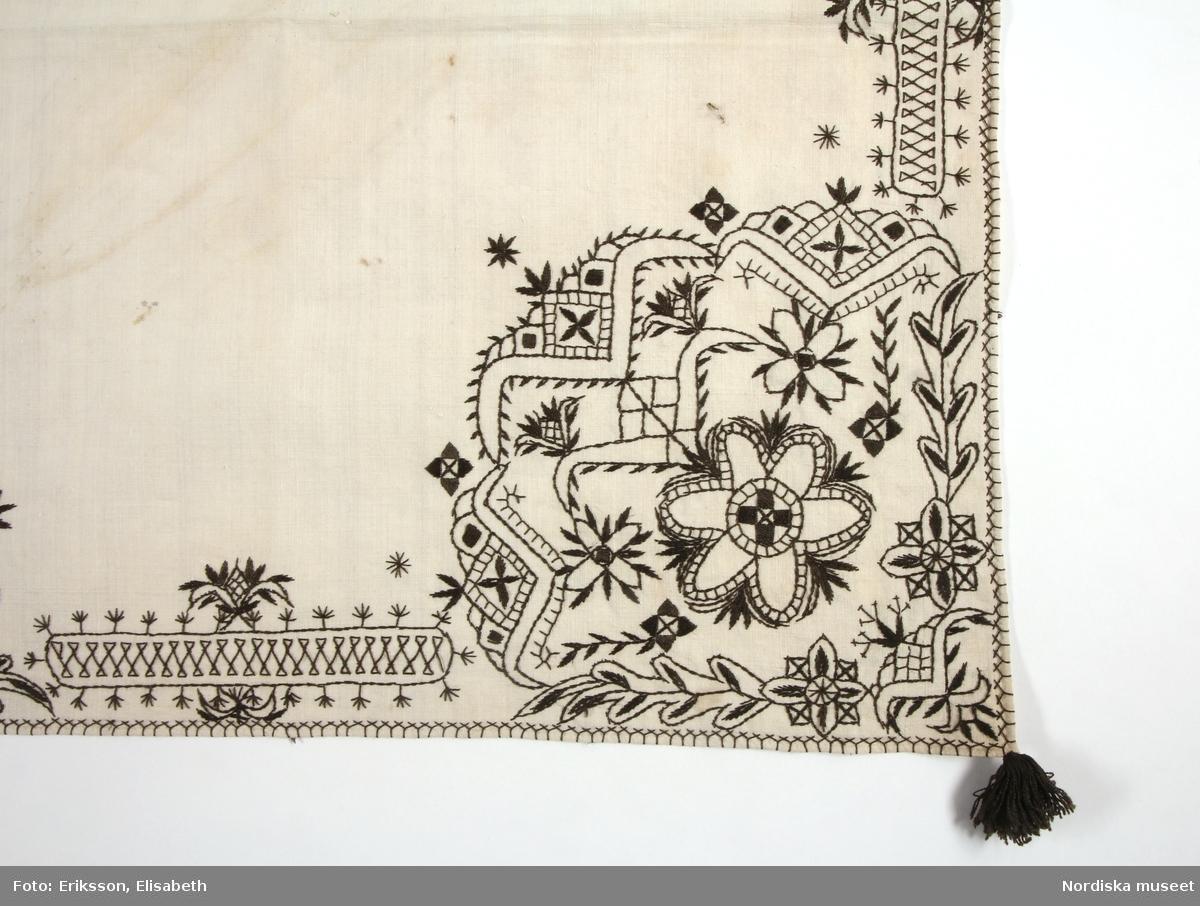 """Huvudliggaren: """"Halskläde fr. Åls sn. Från nedre Heden. Märkt: 'B'""""  Bilaga: Inget utöver huvudliggaren.  Utdrag ur katalogkort: """"Jämför Leksand 39 544 och Gagnef 93,367. I Norge t ex i Voss (15236) och Hardanger hafva liknade plagg brukats till festlig utstyrsel.""""  Halskläde av vit tuskaftad bomull. Fyrkantig duk med broderat mönster, 'krus' i brunsvart silkegarn. Broderat på den sida som syns när klädet viks diagonalt till en tresnibb. Större hörnmotiv i fritt broderi, blommor och bladslingor i plattsöm, stjälksöm och langettsöm. Kantbårder utmed två sidor i flätsöm, stjälksöm och tofssöm. Brunsvarta silkestofsar i alla hörn. I det ovikta hörnet är huvudmotivet placerat, detta upprepas sedan halverat på båda snibbarna. Fållen översydd med  flätsöm i kryss i brunsvart silke utmed två sidor och en bit en på följande. Den del som inte var synlig utåt är märkt med bokstaven """"B"""" i hörnet. Anm: Gulnat något i mittvikningen.  Svartstick är ett broderi som förekommer i några socknar runt södra Siljan i Dalarna. Det broderas som dekor på vita halskläden till folkdräkten.  Utdrag ur Odstedt Ella, (1953), Övre Dalarnas bondekultur under 1800-talets förra hälft. 4.Folkdräkter i övre Dalarna. Sid 306: """"I Ål angav man som regel för bärandet av silkesstickadhalsklädet att det skulle bäras när man bar silkeshätta, alltså även här enbart på de största högtidsdagarna och på brölop."""" /Inga-Lill Eliasson 2007-09-17"""