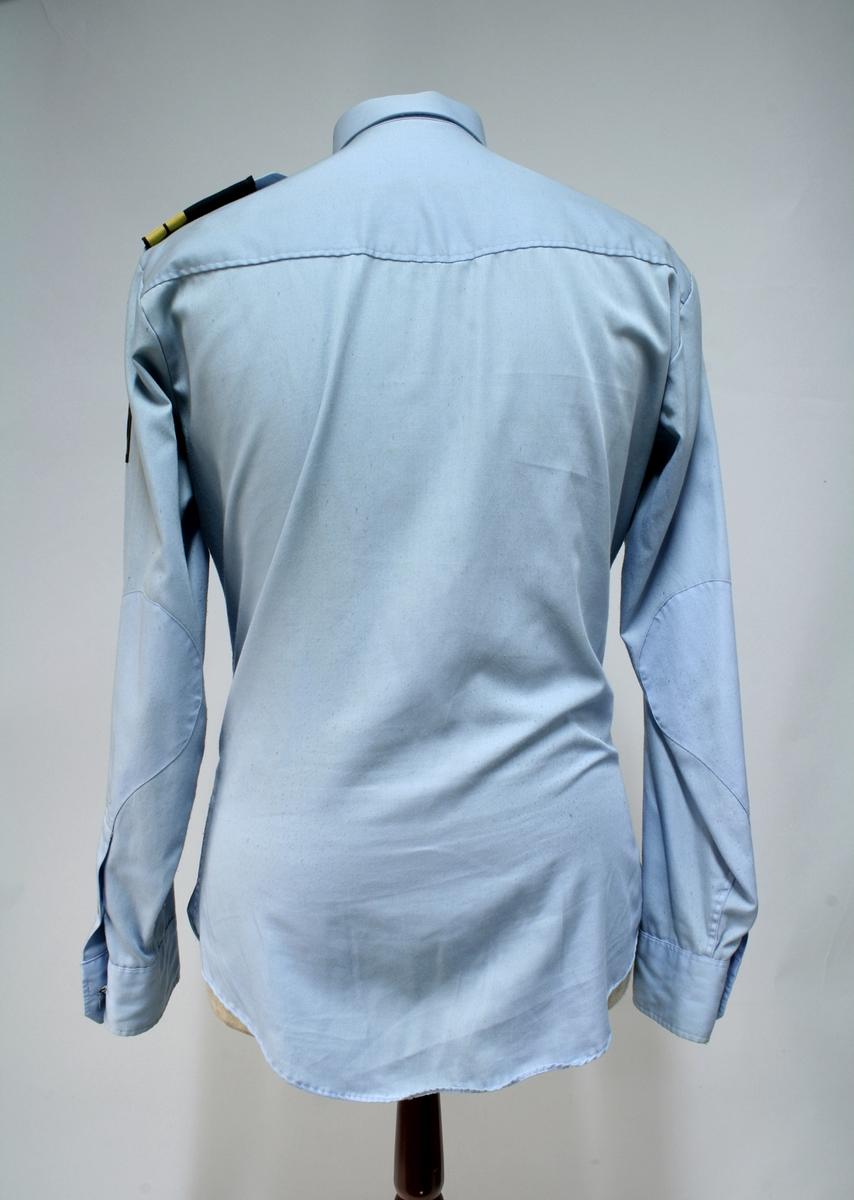 Uniform for politinspektør etter 1963-reglement med merking etter 1977-reglement. Helårsuniform M/1963 med skjorte, langbukse, belte, helårskappe og jakke. Skyggelue med gullbrodert bånd, loslue og båtlue M/1967. Kappen og jakken har skulderklaffer av flettede gullsnorer med to sølvstjerner og festeknapp i gullbroderi. Skjorten har en enklere skulderklaff med to gule render og to sølvstjerner. Det følger med et ekstra enkelt lærbelte og et ekstra sett skulderklaffer til skjorte. Plaggene har gullfargede løveknapper.