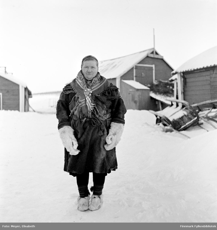 Berit Nilsdatter Hætta fotografert ute vinterstid i Kautokeino-området. Berit har på seg vinterklær, pesk og votter av reinsdyrskinn, samisk sjal med sølje i halsen og samisk lue. På føttene har hun skaller med skallebånd. I bakgrunnen sees en låve og en slede ligger veltet i snøen til høyre i bildet.