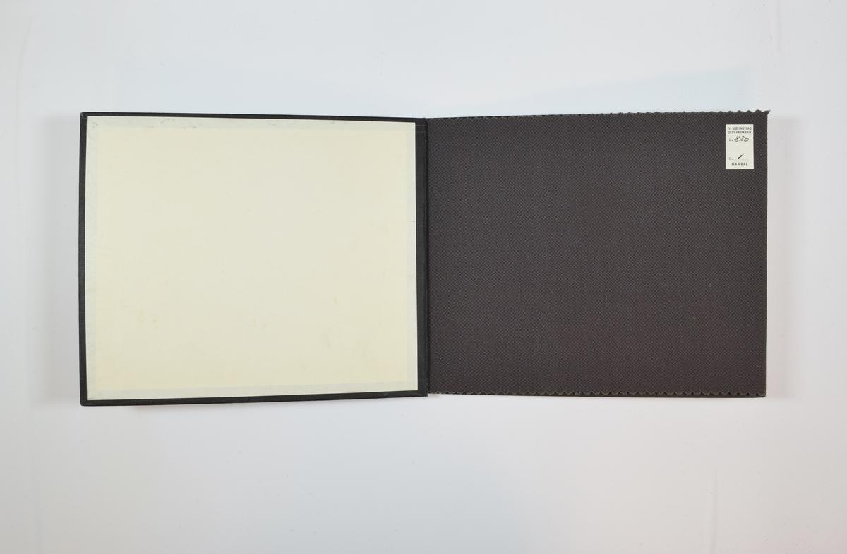 Prøvebok med én stoffprøve. Relativt tynt ensfarget grått stoff med diskret skrå striper i vevmønsteret. Kyperbinding/diagonalvevd. Stoffet ligger brettet dobbelt i boken slik at vranga dekkes. Stoffet er merket med en firkantet papirlapp, klistret til stoffet, hvor nummer er påført for hånd i et trykket skjema. En papirlapp på innsiden av baksideomslaget gir informasjon om stoffet.   Stoff nr.: 820/1