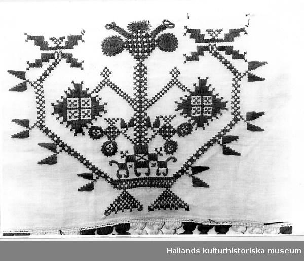 """Hängkläde av linne med röda hallandssömsbroderier. Vita bomullsband i form av hällor är fastsydda i överkanten. Märkning, broderat: """"EBBD"""", """"1853"""". Frans +:70 mm."""