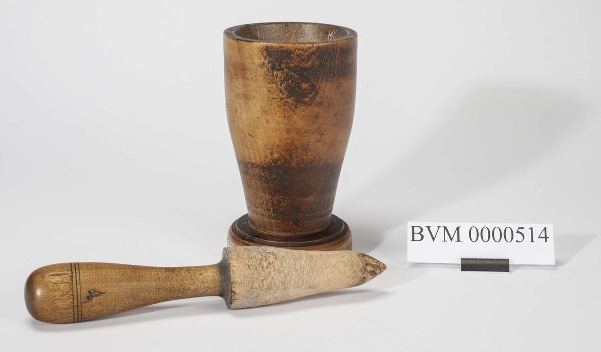Kaffekvern bestående av morter og pistil i dreid tre. Morteren har form som en pokal.