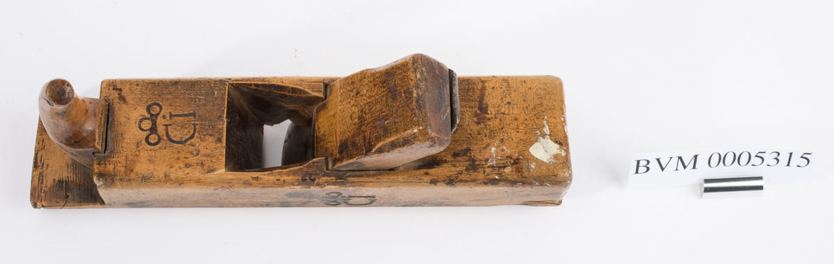 """Høvel i tre med horn/håndtak, kile og høveljern. Jernet er av merket """"I & H SORBY"""". Mellom horn og flisrom og på venstre langside er det stemplet inn ei stilisert krone med CI under (Carl Johan)."""