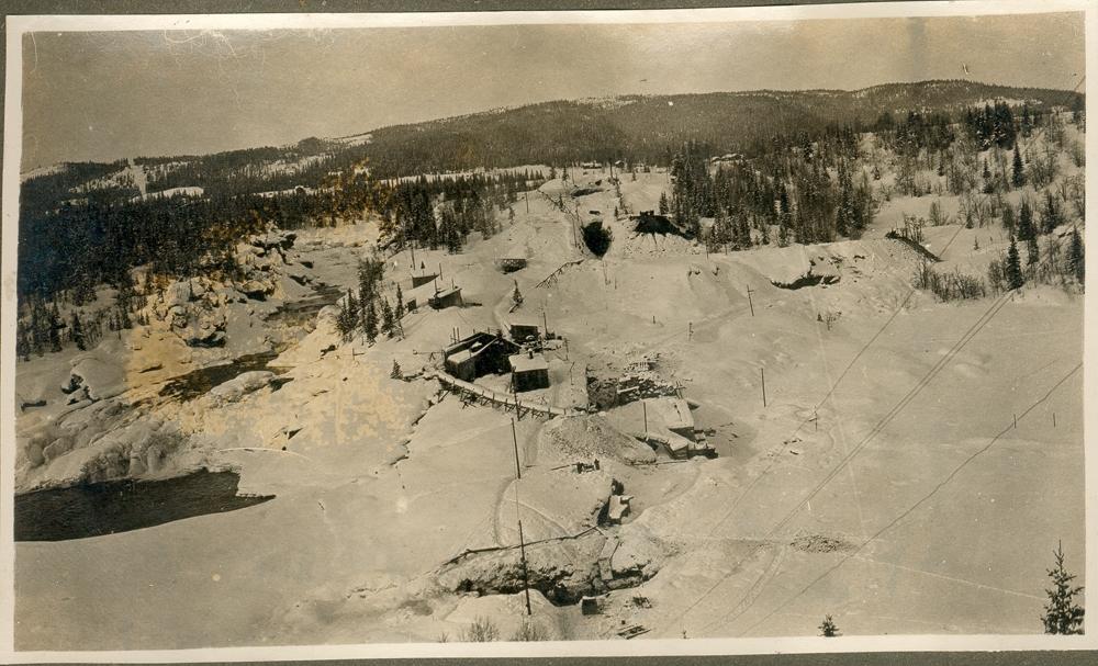 Landskap. Vinter. Skog og fjell. Noen bygninger ved en elv. opplysn: Renfossen under utbygningen 1920-1922.