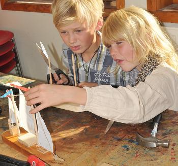 Barn som bygger seilbåt i barnas båtverksted på Norsk Maritimt Museum