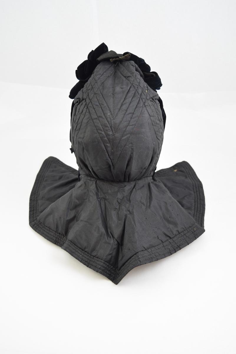 Sort silketaft, vattert, sort bomullsfor. Blå fløyel danner tunget ramme om ansiktet og sløyfe over pannen hvor der også er sløyfe av bomullssateng.  4 og 4 stikninger danner rutemønster på selve luffen. Kraven går bak ned i spiss, 4 stikninger i kanten. Knyttebånd av bomullssateng.