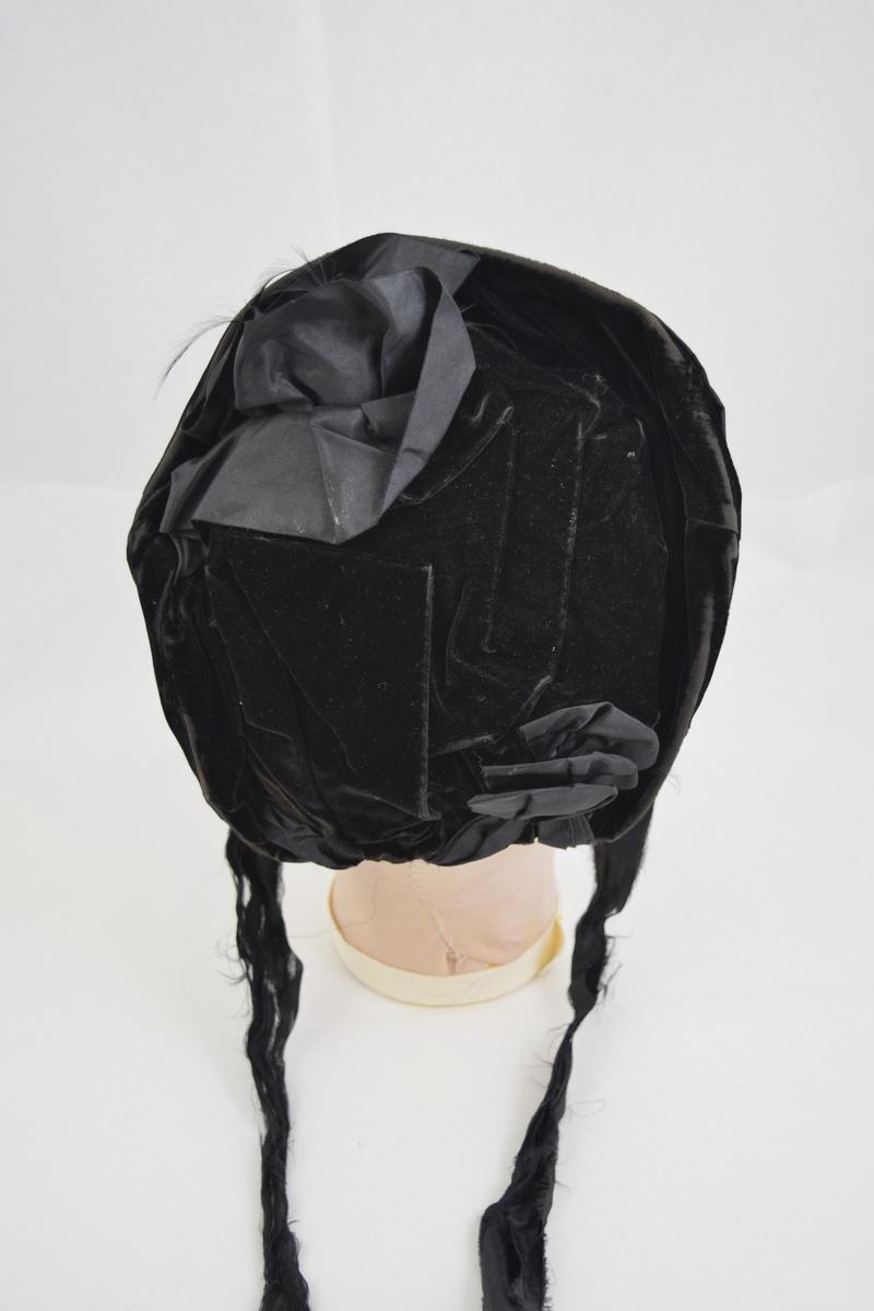 Buet og formet etter hodet, foret og avstivet med polstring. Lange knytebånd, bred kant rundt ansikt og kort avslutning bak. Stoffet er dandert i legg; bak to rosetter.