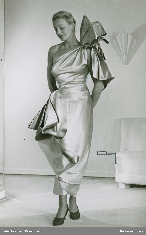 Modell i klänning av Jacques Griffe med stora garneringar vid axeln och höften.