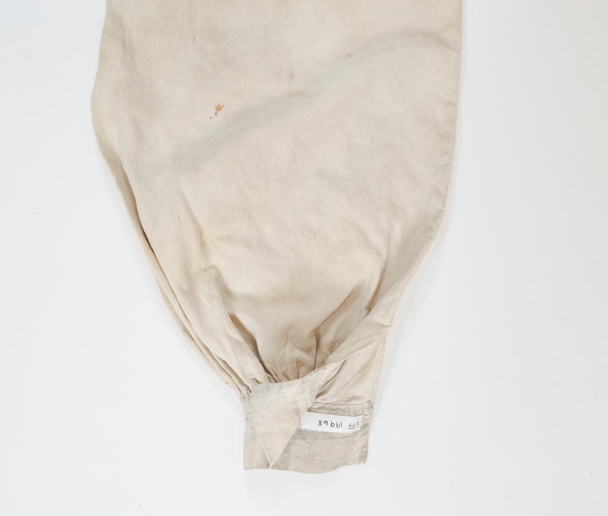 Del av skjorte, erme. i ubleikt lin. Små legg, 3-4 mm, øverst på erme, striper ved ermlinninga. Knapp (kvit, del i to) og knappehol. Handsydd.