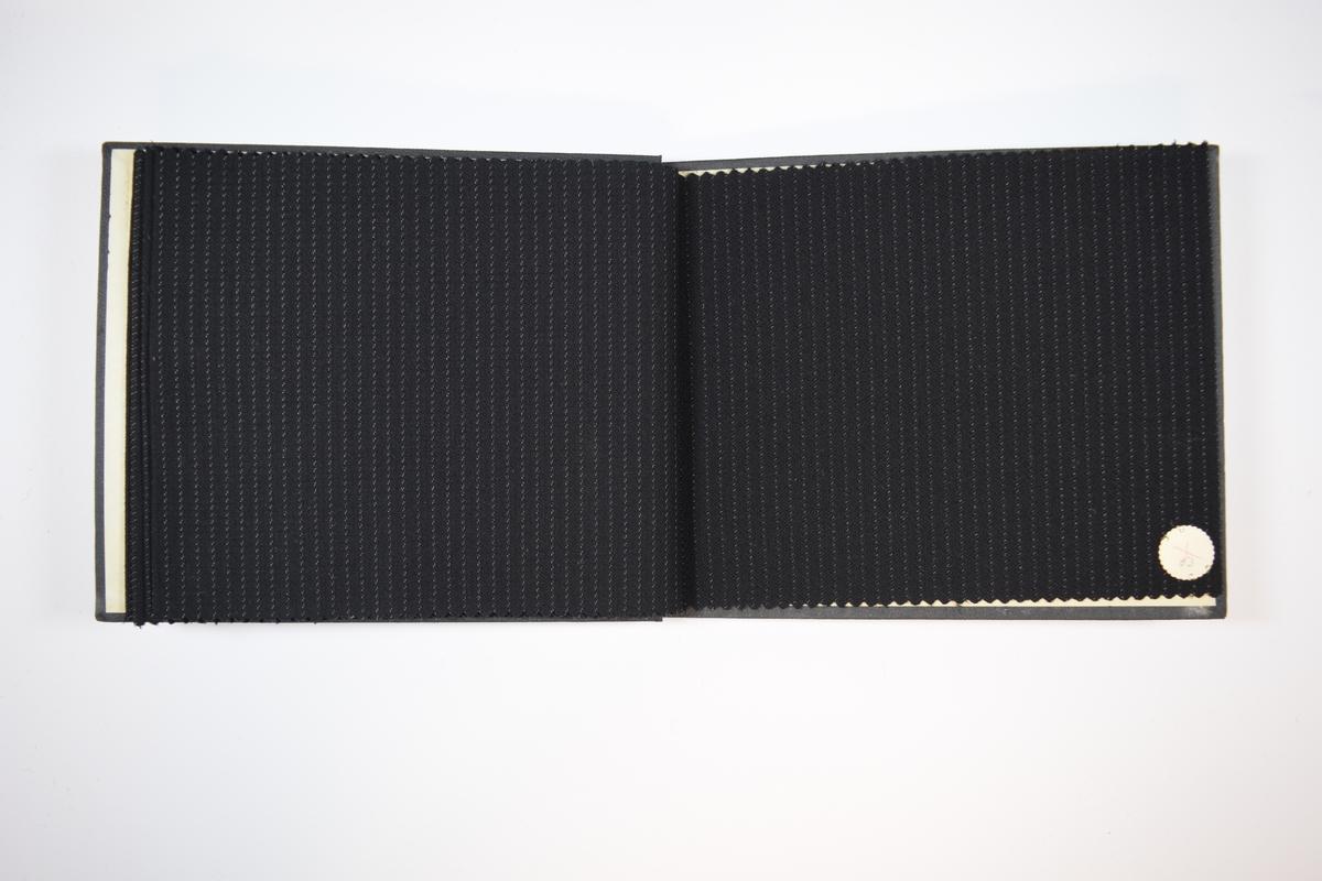 Rektangulær prøvebok med harde permer og fem stoffprøver. Permene er laget av hard kartong og er trukket med sort tynn tekstil. Boken inneholder relativt tynne og tette, mørke stoff med ulike stripemønster. Kyperbinding/diagonalvev. Stoffet ligger brettet dobbelt i boken slik at vranga skjules, men mønsteret er det samme på baksiden. Stoffet er merket med en rund papirlapp, festet til stoffet med metallstifter, hvor nummer er påført for hånd. Innskriften på innsiden av forsideomslaget indikerer at alle stoffene i boken har kvlaitetsnummer 4600.   Stoff nr.: 4600/49, 4600/50, 4600/51, 4600/52, 4600/53.