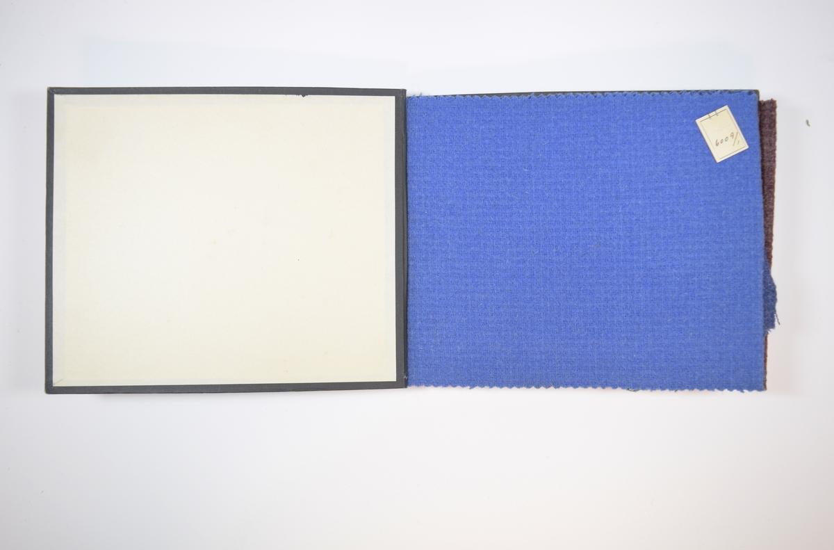 Rektangulær prøvebok med harde permer og fire stoffprøver. Permene er laget av hard kartong og er trukket med sort tynn tekstil. Boken inneholder relativt tykke ensfargede eller melerte stoff med rutemønster eller lignende i veven. Bindingen sees tydeligere på baksiden. Stoffene ligger brettet dobbelt i boken slik at vranga skjules, men mønsteret er det samme på baksiden. Stoffene er merket med en firkantet papirlapp, festet til stoffet med metallstifter, med nummer påført for hånd.  Stoff nr.: 6009/1, 6009/2 6009/3, 6009/4.