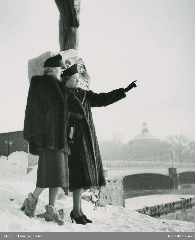 Två modeller i minkpäls och hatt, står vid bro och tittar ut över vattnet.
