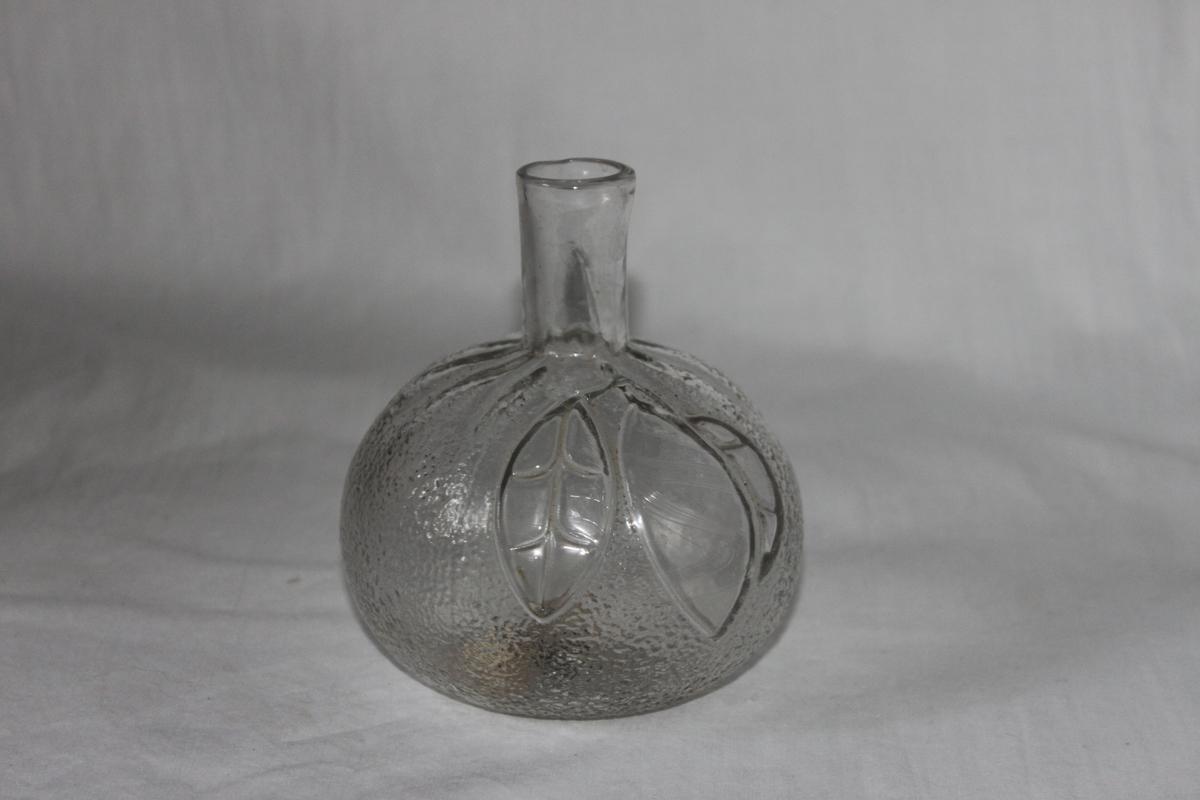 Vas/flaska i form av en stor apelsinliknande frukt, knagglig yta med bladkvist. 40 mm hög hals med diam. 20 mm