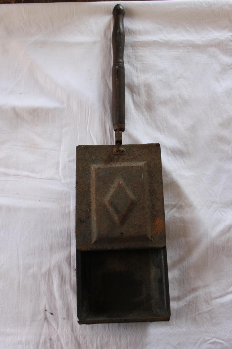 Kafferostare av järn, består av en rektangulär, skaftförsedd låda med draglock och dragstång som avslutas med en krok. I locket syns en pressad rektangel och i denna en romb. 285 mm långt skaft av trä.
