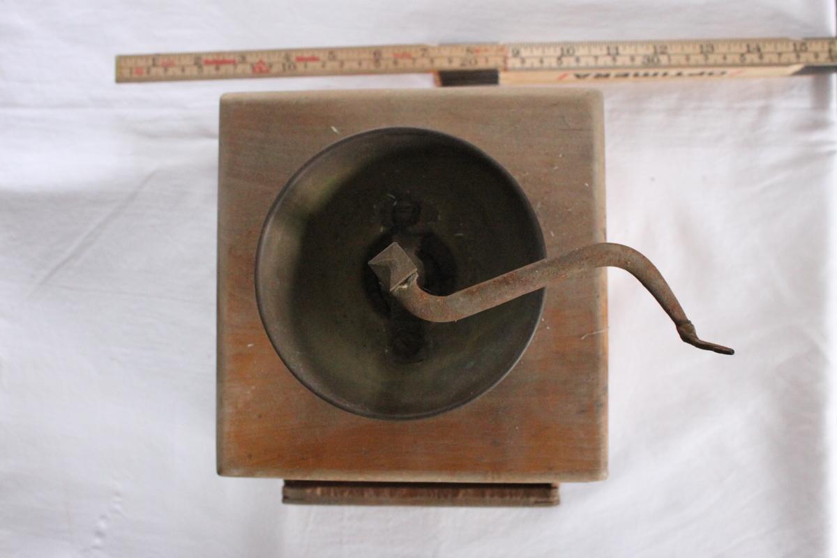 Kaffekvarn av trä med kubformad behållare innehållande en draglåda med platt träknopp. Ovanpå behållaren är en skål av mässing fästad med skruvar. I mitten en vinklad vred av järn som i motsatta änden har  en kvarn som roterar under skålen. Vreden saknar handtag/knopp.