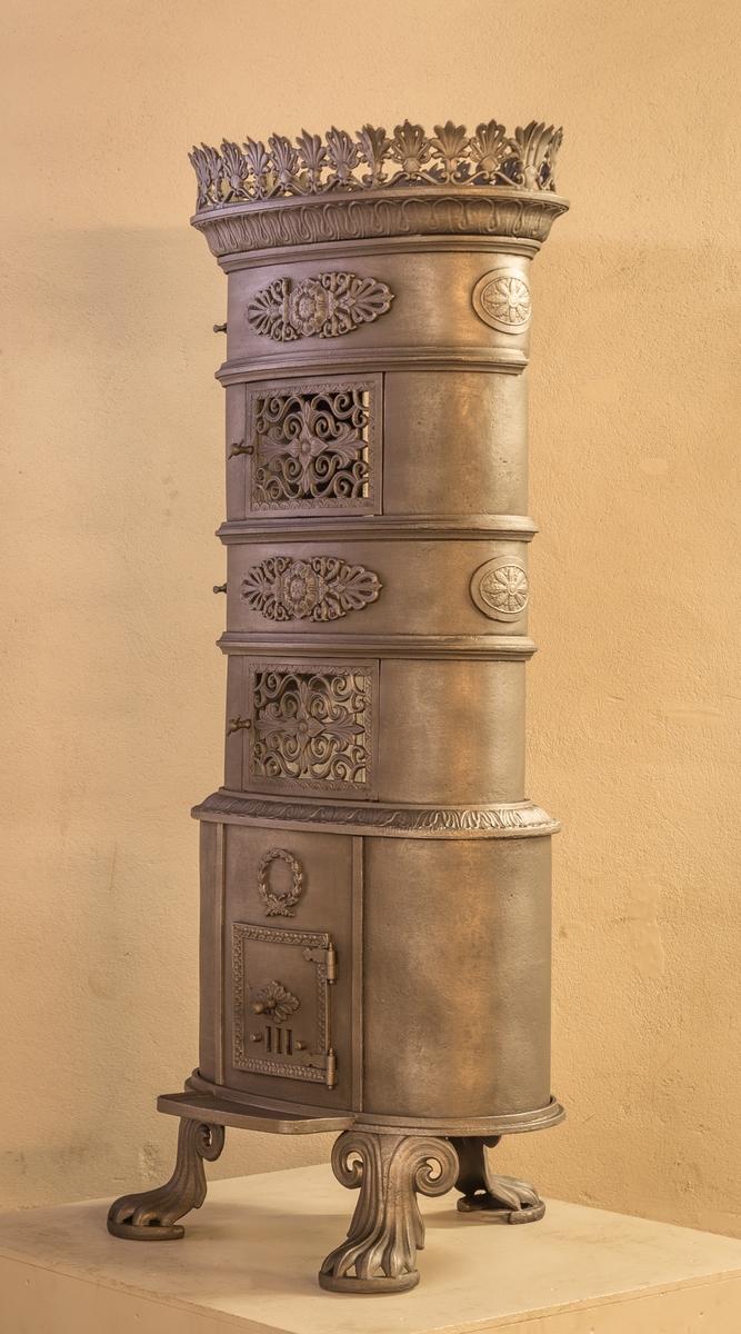 """Tre etasjes oval ovn i Biedermeier stil. Ovnen står på tre """"dyreføtter"""". Ovnsdøren er plassert på langsiden. En ventil og en gjennombrutt mønstrende gitterdør i hver etasje over brennkammeret. Ovnen avsluttes med en krans på toppen. Ovnen har store slette flater og dekorert med rosetter og palmetter. Merket med verkets navn på brennkammerets bakplate."""