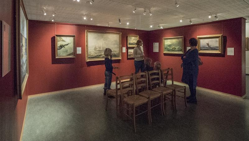 Museumsansatt, tre barn og en voksen foran skipsmalerier. (Foto/Photo)