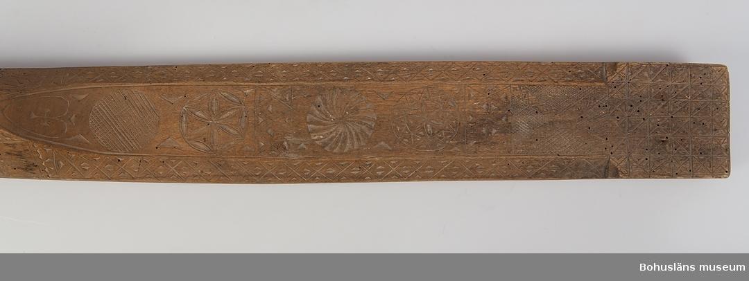 """Platt, rektangulärt redskap med handtag i ett stycke. Det har avfasade långsidor med ett kvadratiskt, rutmönstrat parti i uddsnitt framtill. De avfasade sidorna har också uddsnittsdekor. Mittdelen är täckt med skuren dekor i form av rosetter, virvelhjul, rutmönster, hjärta samt geometriska mönster i uddsnitt. Vid handtaget är årtalet """"1849"""" inskuret på en av sidorna. Är en friargåva. Kavelrullen att linda tyget runt saknas. Har mörknat på grund av användning. Defekt framtill efter skadedjursangrepp.  Litt.; Nylén, Anna-Maja, Hemslöjd, Håkan Ohlssons förlag, Lund, 1978, s. 359-363. Fredlund, Jane, Stora boken om livet förr, ICA-förlaget, Västerås, 1981, s. 40-49, 170-177. Sörensen, Steinar, Mangletreet-Glatteredskap og festegave, Glomdalsmuseets småskrifter nr. 3, Engers Boktryckeri A/S, Otta.  Ur handskrivna katalogen 1957-1958: Kavelbräde. dat. 1849 Mangelbräde. L. 67 Br. 9,5 Trä med karvsnittsmönster. Obetydligt skadad. Maskhål.  Lappkatalog: 72"""