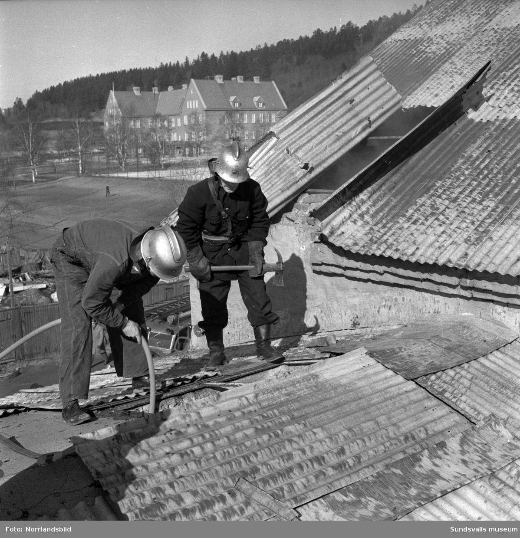 Ett par brandmän med hjälmar och yxor bryter upp taket för att bekämpa en eldsvåda i en gammal industribyggnad vid Fabriksgatan. I bakgrunden syns Västhagens sjukhus.