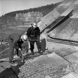 Ett par brandmän med hjälmar och yxor bryter upp taket för a