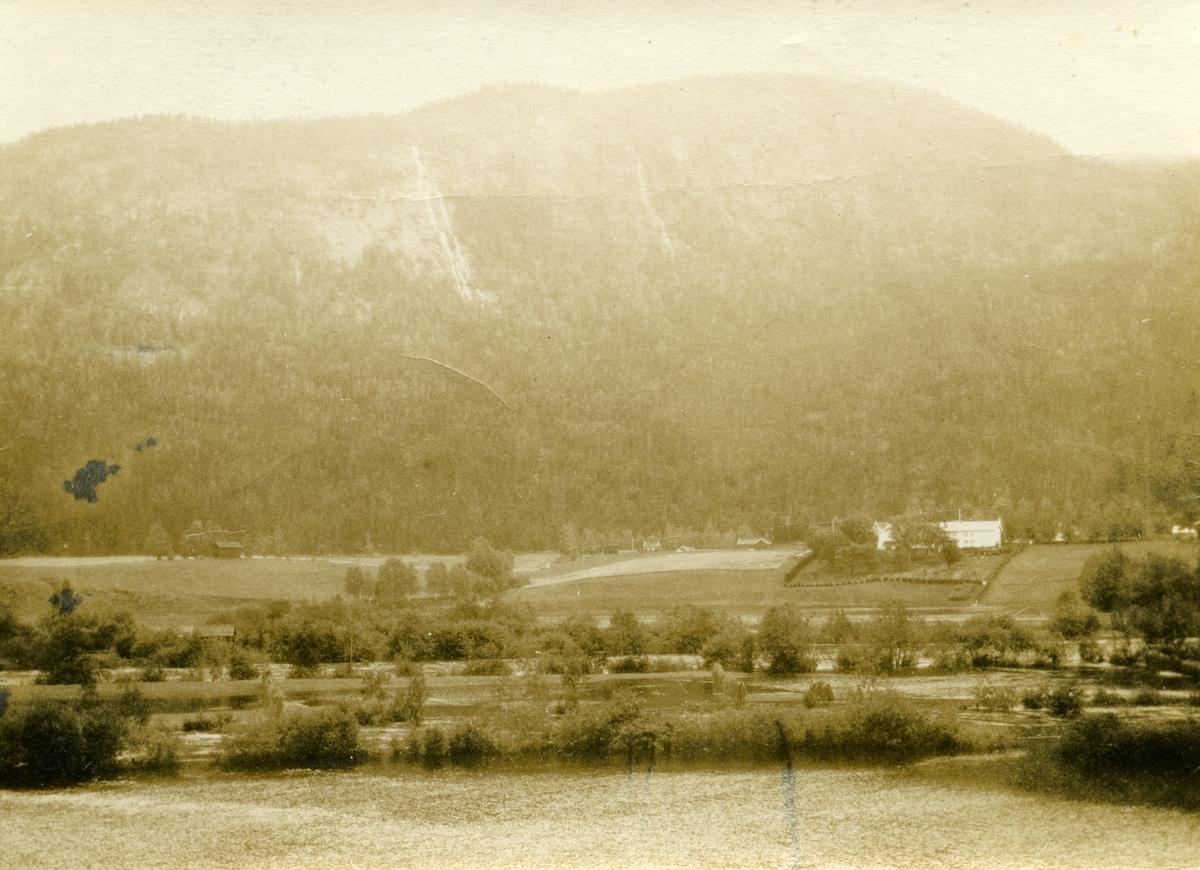 Landskapsbilde med gården Haugsrud på andre sida av elva.