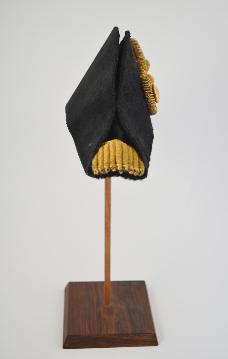 A) Hatt. Sort, velurlignende. Kokarde, gulltresse m/gullknapp pyntet med ørn. Gullpynt, gulltresser i begge snuter, samt en hvit og en rød snor vekselsvis under gullsnorene. Sort silkefor.   B) Hatteeske i blå papp.