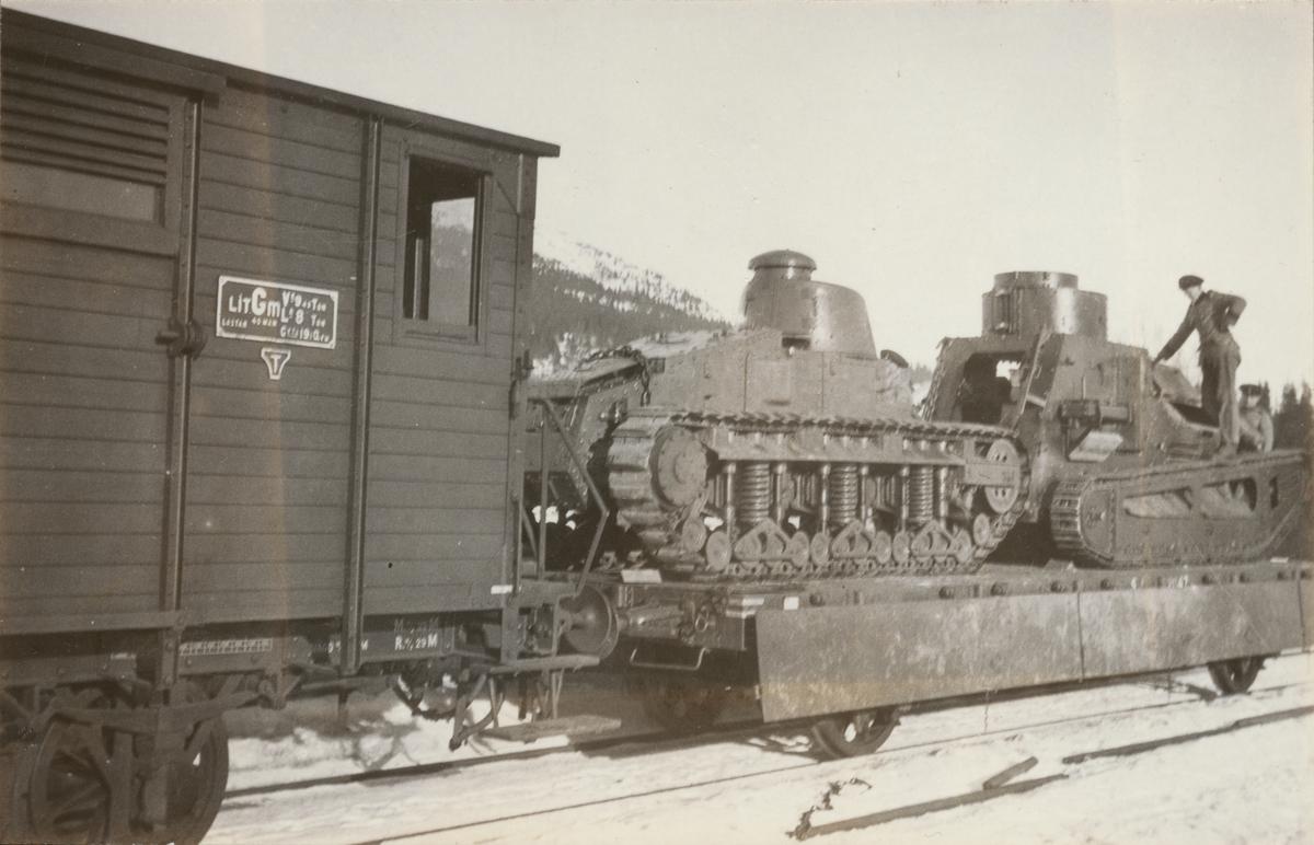 Två stridsvagnar m/1921 (eller m/1921-1929) lastade på tåg. Två soldater står och kontroller lastningen.