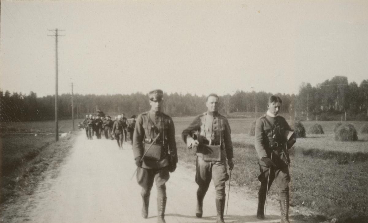 Deltagare i stridsvagnskursen vid Göta livgardes stridsvagnsbataljon marcherar på landsvägen. Närmast kameran (från vänster) löjtnant de Maré Dalregementet I 13, löjtnant Holmgren Göta livgarde I 2 och löjtnant Festin Livregementets grenadjärer I 3.