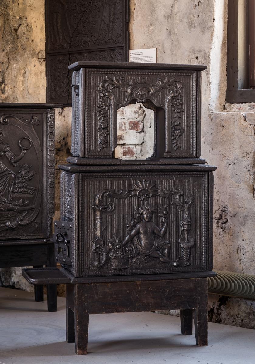 """Etasjeovn med """"putto"""" - naken barnefigur- med blomster på begge langsider 1.etg. Ovnsluke på kortside 1.etg. Langside 2.etg har uregelmessig åpning med symmetrisk blomstrende rokokko-ornamentikk. Alle plater har riflet bunn og springlist-ramme."""