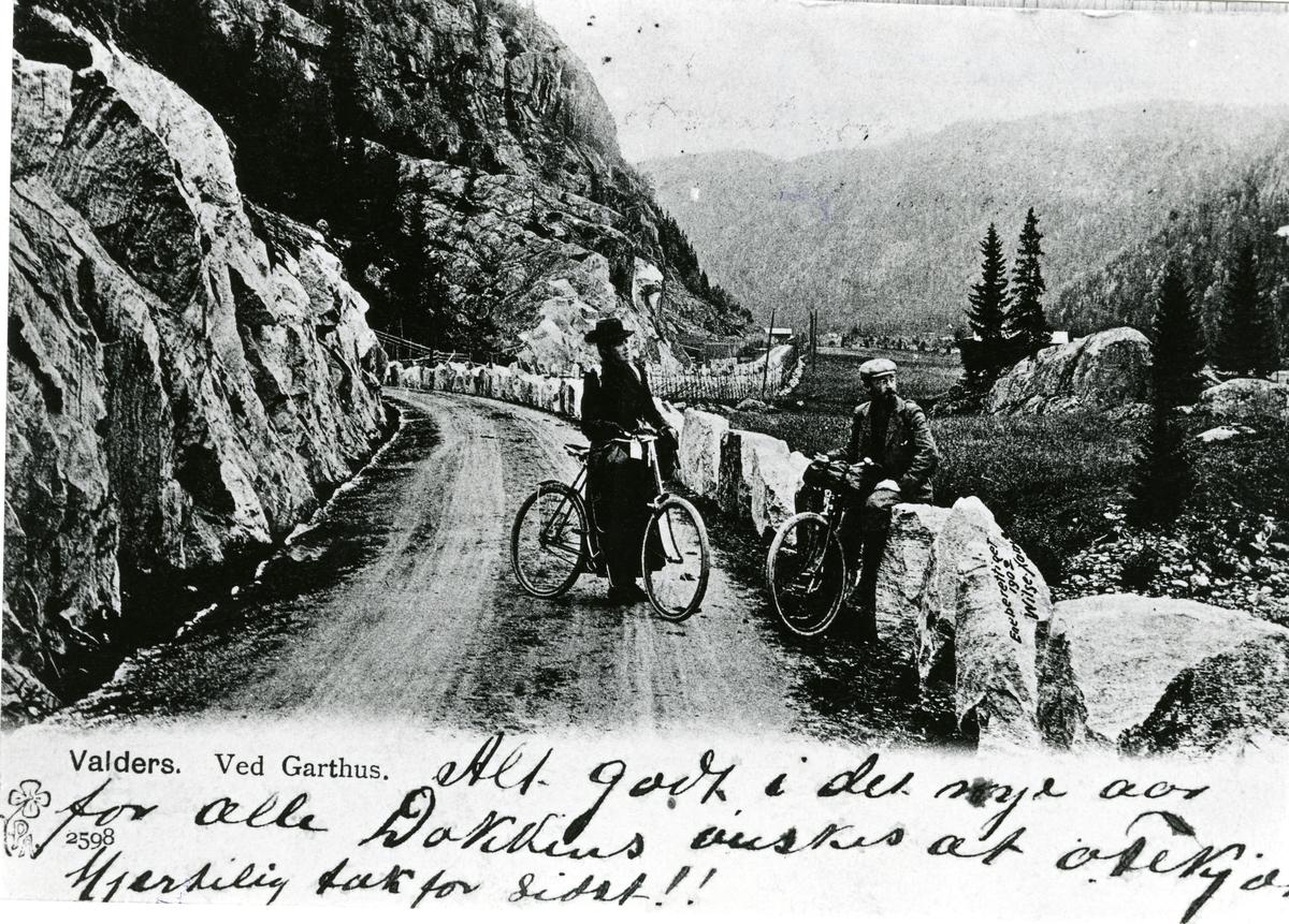 En kvinne og en mann avbildet med hver sin sykkel ved Garthus i Sør-Aurdal.