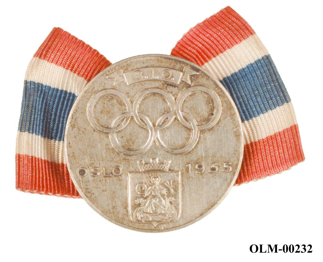 Sølvfarget merke med Oslos byåpen St. Hallvard, innskriften Oslo 1935, de olympiske ringene og C.I.O. Merket er festet på et bånd med det norske flaggs farger.