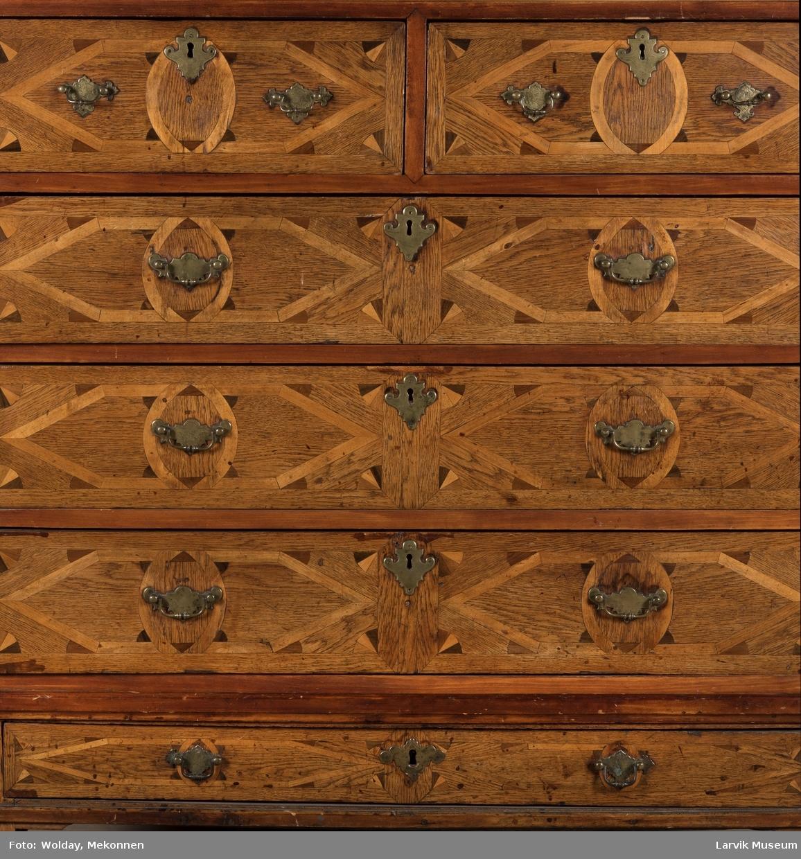 Dragkiste med 6 skuffer,utstående list over nederste,kuleben. Intarsia  på skuffer og kortsider.