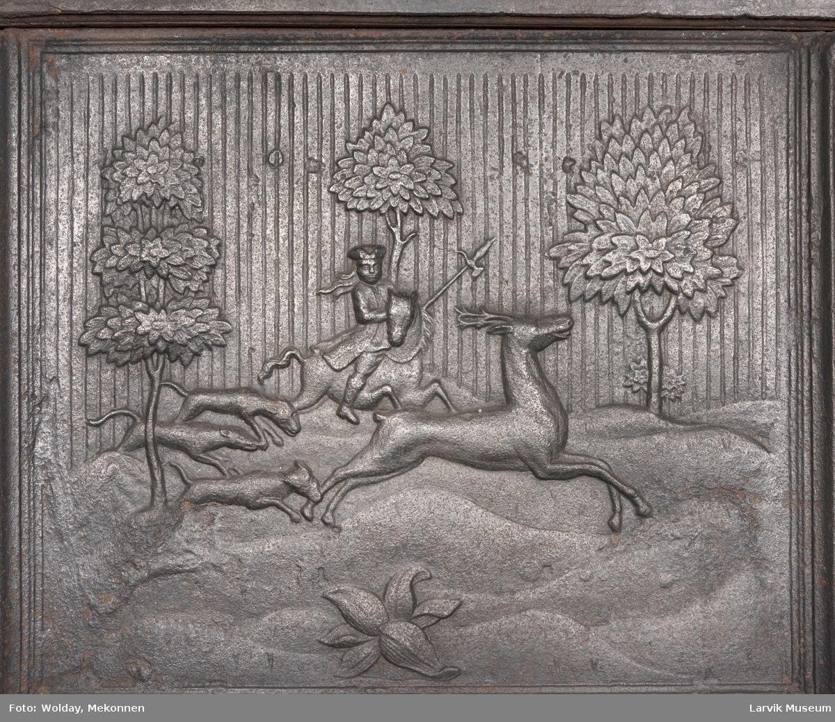 Buet askebrett.  1. etsje langside: Jeger til hest med tre hunder, jager en hjort i kupert terreng med trær.  1. etasje kortside:  Fliket bladverk, laurbærkrans. 1. etasje kortside: Under fliket bladverk, dør med gjennombruttlufteåpning.  2. etsje langside: Rocaille-ornamentikk. 2.etasje kortside: Stor vase med blomster alle sider untatt bakre kortsider. 1.etg. riflet bunn. jfr. 485c i Norsk Jernskulptur II.