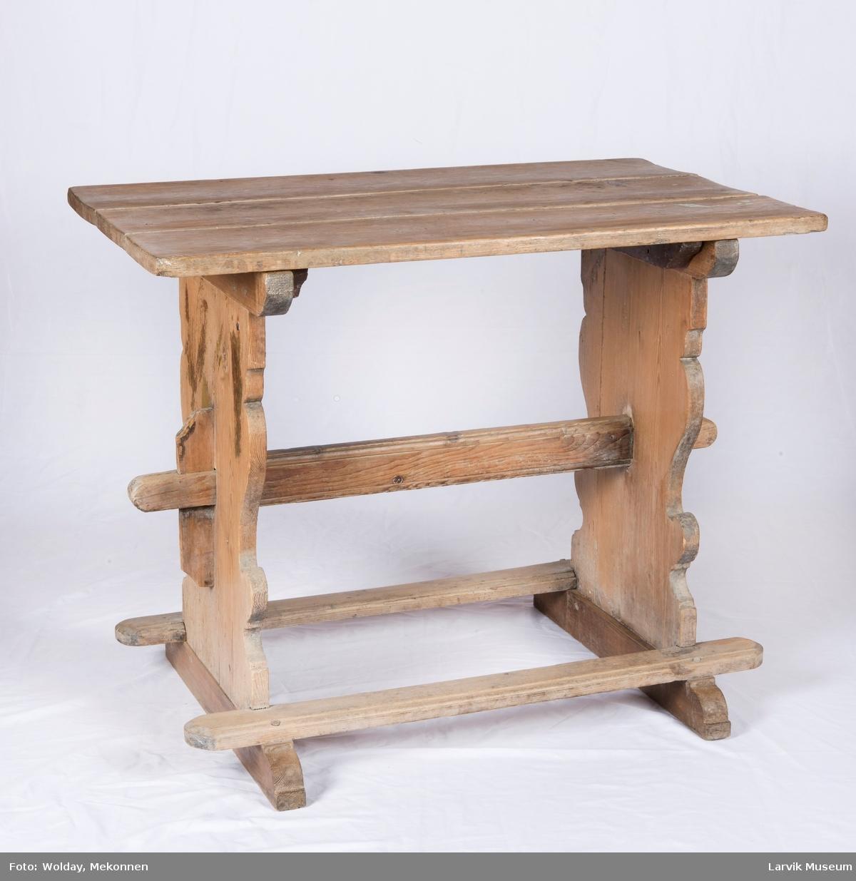 Bordet har rektangulær bordplate sammensatt av 3 deler skårede vanger forbundet med profilert strekkfisk festet med blei, 2 profilerte fotlister festet til sokkel med trenagler
