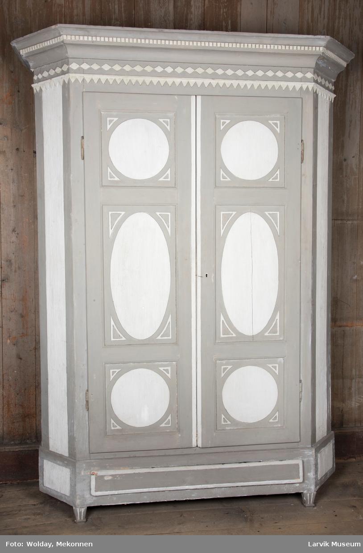 Skap med to dører, 5 hyller hyller, dører med ovale og sirkulære riflete speiler på dørene, 4 kannelerte ben, hengslene og lås av jern og en skuff nederst.