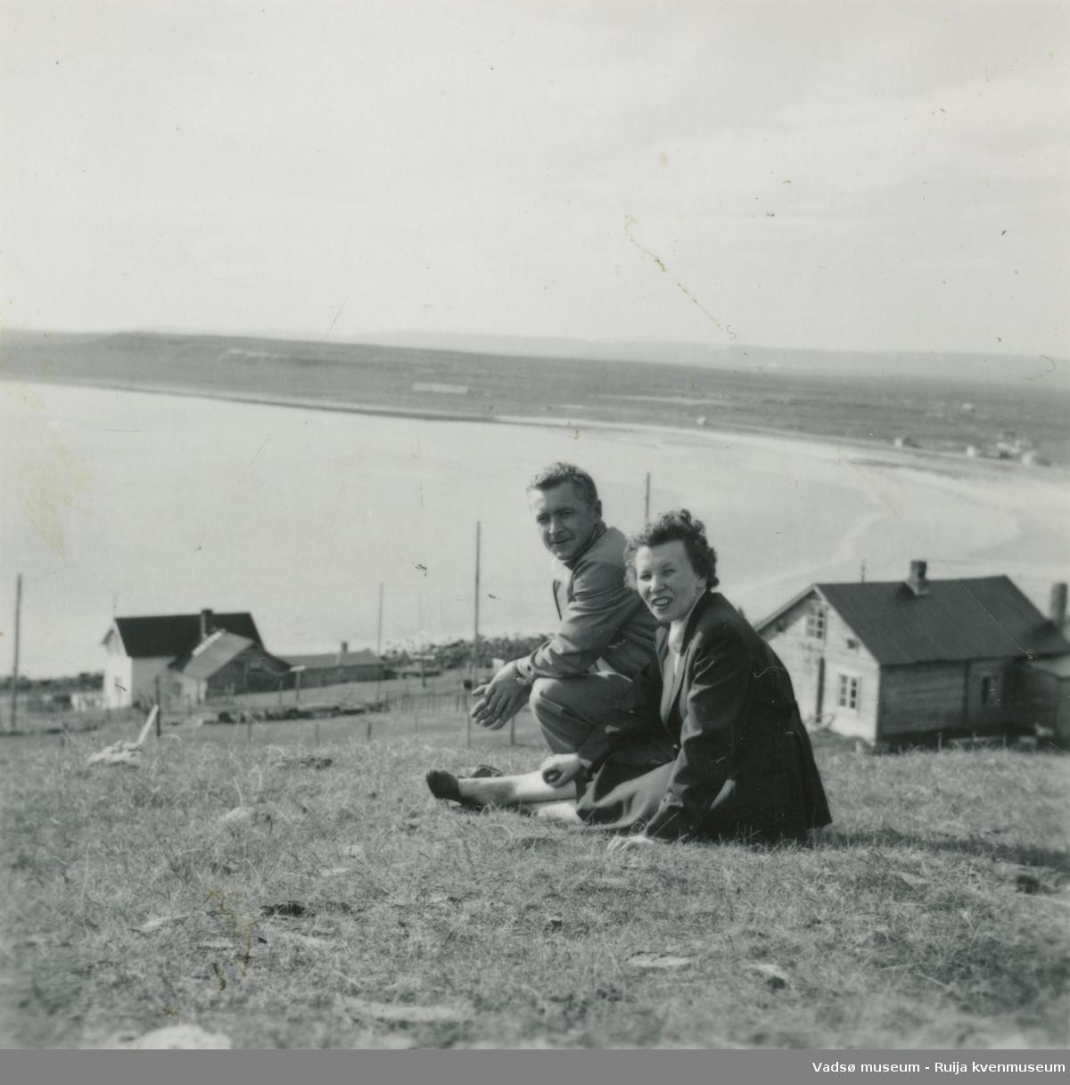 """Reidun og Paul Gundersen avbildet sittende på marka på """"Bakkan"""" i Ekkerøy.  Varangerfjorden i bakgrunnen."""