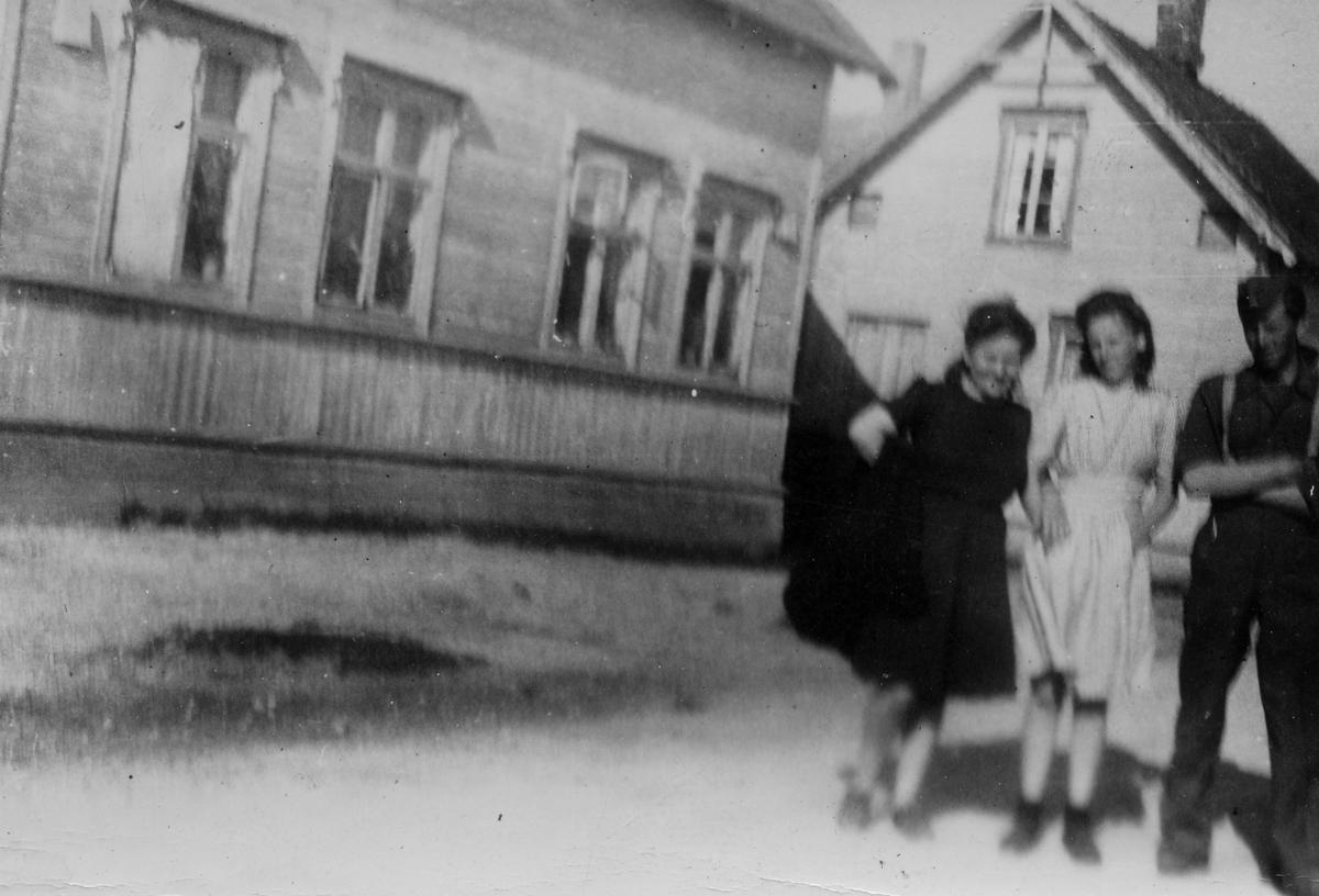 To jenter og en ung mann avbildet i gate i Vadsø. Flere trebygde bolighus i bakgrunnen.