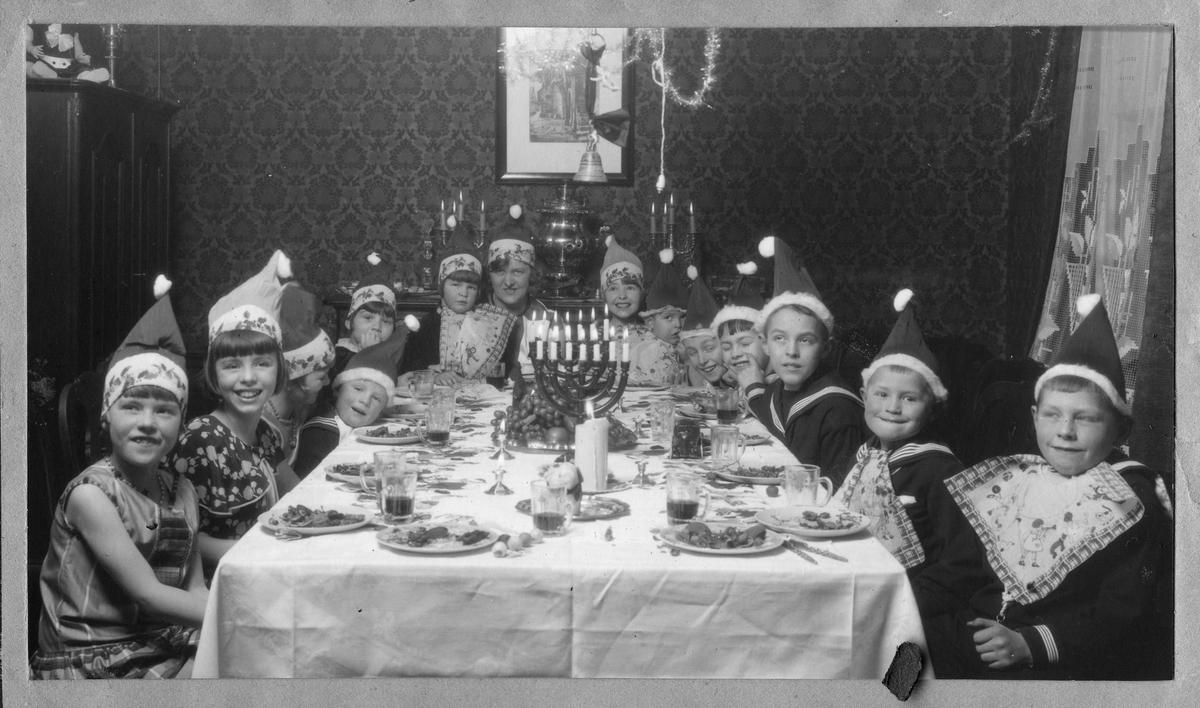 """Barn rundt bord med nisseluer i juleselskap. Bildetekst""""Juleselskap hos Dr. Cappelen, 1928"""" Ranghild"""