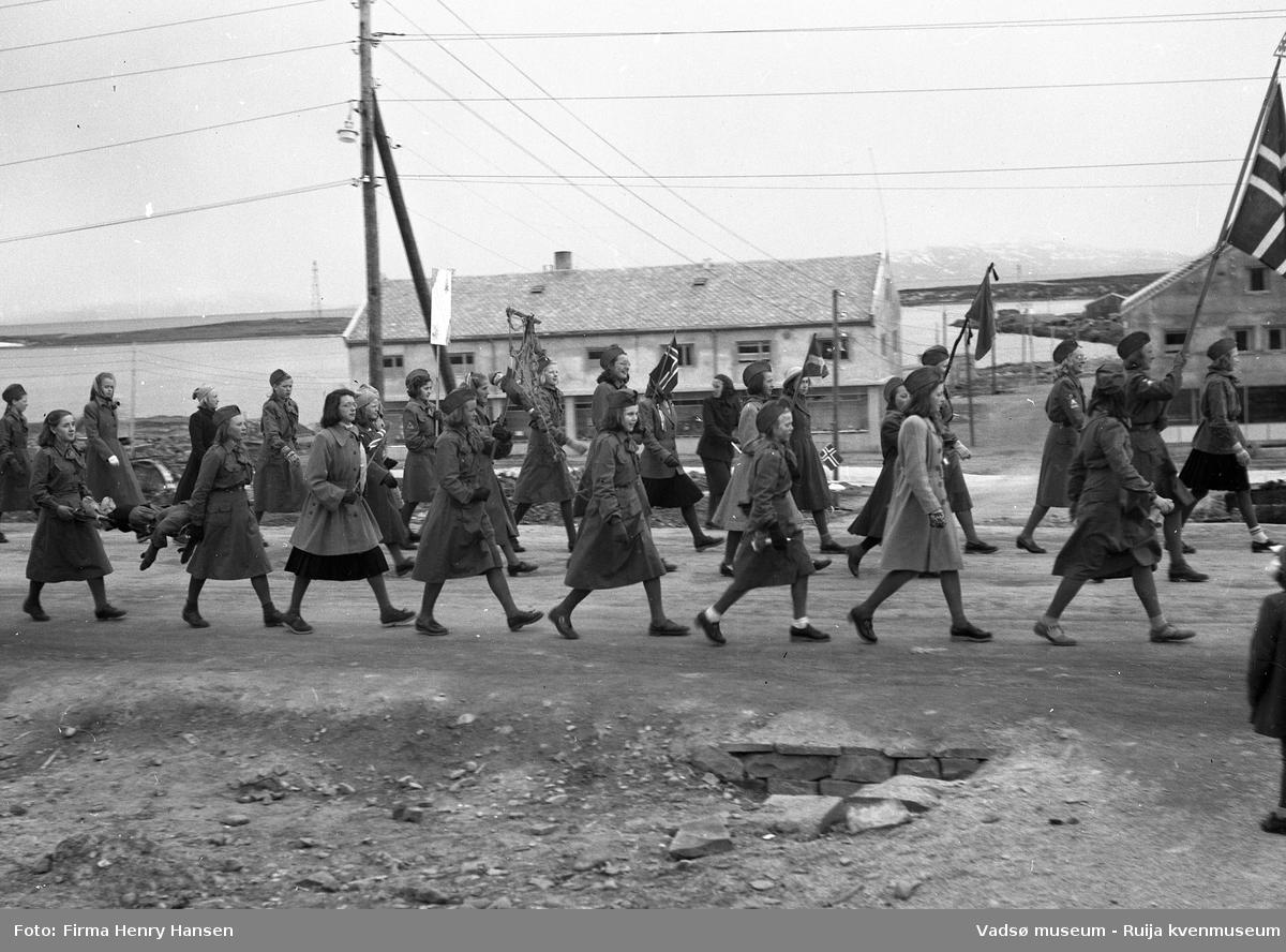 Vadsø sentrum 1951. Del av 17.maitog i Hvistendalsgate. Bildet viser ca. 20 jenter, noen i uniform og alle med speiderlue fotografert fra nord. I bakgrunnen sees Luftskipsmasta på Vadsøya og forretningsbygg under bygging: Torleif Mathisen og Leif Bjerck.