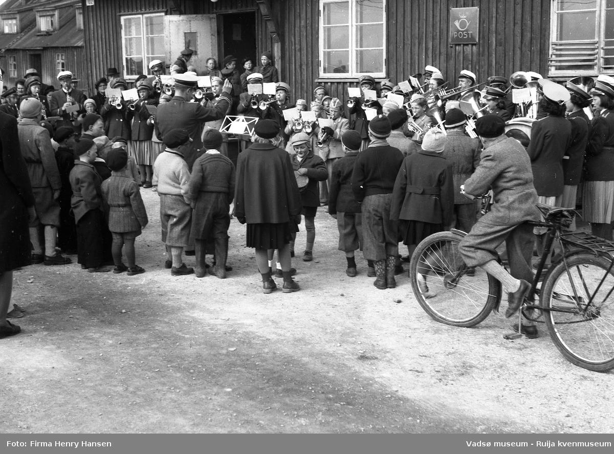 """Vadsø sentrum 17. mai 1951, Musikkorps står oppstilt og spiller, jenter, gutter og voksne, med dirigent. Aksel Niska er helt til høyre i korpset. Flere barn står foran korpset med ryggen til, en av guttene har sykkel. Korpset står foran postbrakka med skilt """"Post """"og nr """"102"""" på veggen. Vi ser litt av nabohuset til venstre, også en brakke."""