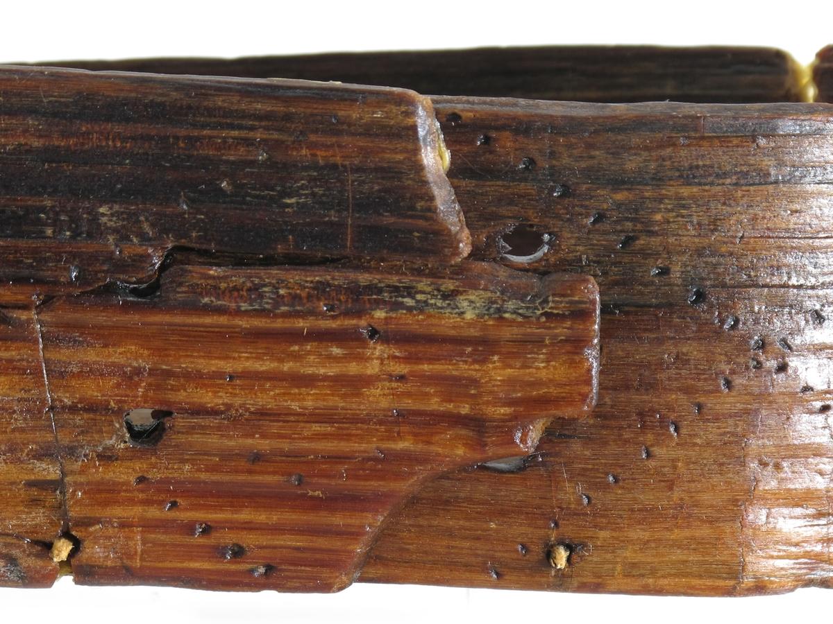 Sponeske med lokk. Sveipet, trolig av lauvtre.  Umalt. Bunn og topp i lokket ovale  trestykker, sider i eske og lokk av spon. Trenagler binder fast bunn og topp. Spona sydd sammen, trolig med tæger, en ser hullene i siden. Sidene har svidekor i enkelt stilisert mønster, kruller. Lokket har siksaker.   Tilstand juni 1979: Svært dårlig. Bitene holdt sammen med voks og lim, koppertråd.