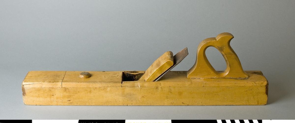 Rubank av bok. Hyveljärn med instansat fabriksmärke ERIK ANTON BERG, ESKILSTUNA, SWEDEN, GARANTI med fabrikens logotyp, en avbildad haj. Ett stycke trä är borta i bakre övre änden av stocken.  Hyveln är märkt med Stockholms Borgargilles nr. SB 1798  Funktion: Släthyvling av längre arbetsstycken