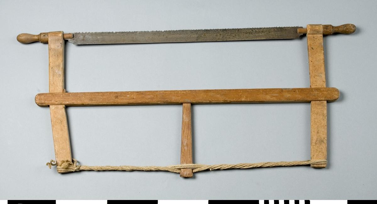 Såg med ställning av trä. Ställningen består av en bom av furu och två sågarmar av bok. Sågbladet av stål är inspänt i ställningen mellan sågarmarna med hjälp av en spännpinne och ett snöre. Genom den ena änden av varje sågarm går en svarvad knopp som är vridbar. Bladet är fäst i denna och kan ställas snett. På bladet är ingraverat SANDVIKENS JERNVERKS AB, SANDVIKEN SVERIGE, EXTRA PRIMA GARANTI, EXTRA TUNNSLIPAD I RYGGEN. No 425. Sågen användes för kapning.  Funktion: Rörlig sågklinga för vågrät och lodrät sågning av skivor