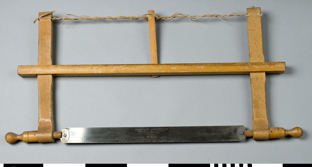 Såg med ställning av trä. Ställningen består av en bom av furu och två sågarmar av bok. Sågbladet av stål är inspänt i ställningen mellan sågarmarna med hjälp av en spännpinne av furu och ett snöre. Genom den ena änden av varje sågarm går en svarvad knopp som är vridbar. Bladet är fäst i denna och kan ställas snett. På bladet är ingraverat SANDVIKENS JERNVERKS AB, SANDVIKEN SVERIGE, EXTRA PRIMA GARANTI, EXTRA TUNNSLIPAD I RYGGEN. No 440, samt Malteserkors (? KK/2002-02-26). Sågbladet är fintandat. På bommen är inristat AV. Snöret trasigt, lösa ändar mitt på snöret. Sågen användes vid sinkning och finsågning.  Funktion: Rörlig sågklinga för vågrät och lodrät sågning av skivor