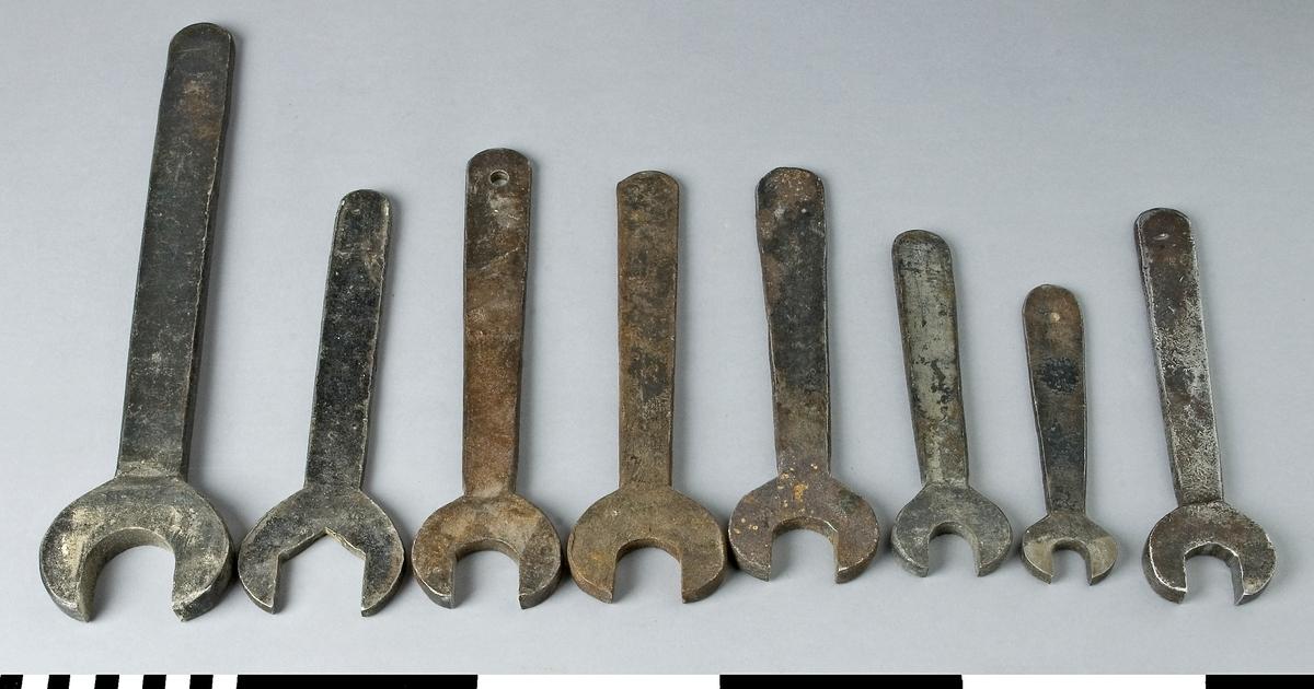 Skruvnyckel av järn, 8 st, avsedda för användning på träbearbetningsmaskinerna på Snickerifabriken. Skruvnyckeln har fast nyckelvidd och är enkel. Nyckelgreppet är öppet i linje med skaftet. De olika skruvnycklarna har nyckelvidd och mått enligt följande tabell, i övrigt är de lika tillverkade.        nyckelvidd   längd   bredd    a)            40         335      83            b)            38         225      72            c)            29         245      65            d)            29         230      68            e)            29         220      65            f)             22         180      50            g)            16         155      40 h)            24         210      55               Funktion: För inställning av olika verktyg