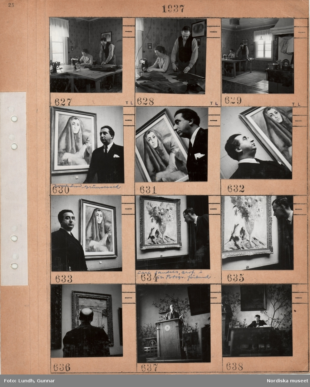 Motiv: Rumsinteriör en kvinna sitter vid en symaskin, en man klipper till dräktdelar i skinn, på väggen hänger mönsterdelar till kläder, järnspis med kokkärl, en man, Isaac Grünewald, står framför en tavla av en kvinna med sjal på huvudet, en man, Carl Sandels ordförande i Svenska fotografers förbund, står vid en tavla av en vas med blommor, man bakifrån betraktar en tavla med hamnmotiv, en man står i en talarstol inomhus, en man sitter vid ett bord.