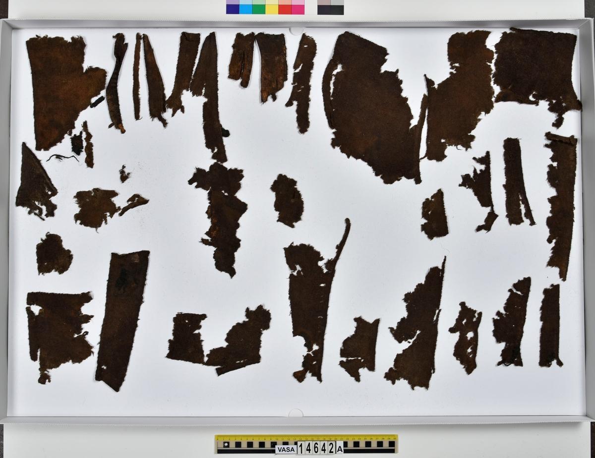 Textil. 132 fragment uppdelade på fyndnummer 14642a-f. Fnr 14642a består av 42 fragment av ull vävda i tuskaft. Tyget har varit valkat på ena sidan. Många av fragmenten har bevarade originalkanter med sömmar och fållar. Fnr 14642b består av 2 fragment av ull vävt i 2/1-kypert. Fragmentet har en bevarad originalkant. Fnr 14642c består av 14 fragment av ull vävda i 2/2-kypert. Flera av fragmenten har en bevarad originalkant. Fnr 14642d består av 28 fragment av ull vävda i 2/1-kypert. Fyra av fragmenten har en bevarad originalkant. Flera av fragmenten består bara av lösa trådar. Fnr 14642e består av 9 fragment (4 större samt 5 mycket små) av ull vävda i tuskaft. Tyget har varit valkat på ena sidan. Fragmenten har bevarade originalkanter med spår av sömmar. Fnr 14642f består av 37 fragment av ull vävda i tuskaft. Flera av fragmenten har bevarade originalkanter med fållar och spår av sömmar.